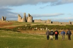 Walkers approaching Dunstanburgh Castle is near George Stephenson's Birthplace