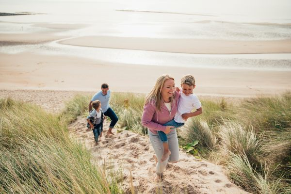Family on beach  is near Cresswell Towers Holiday Park