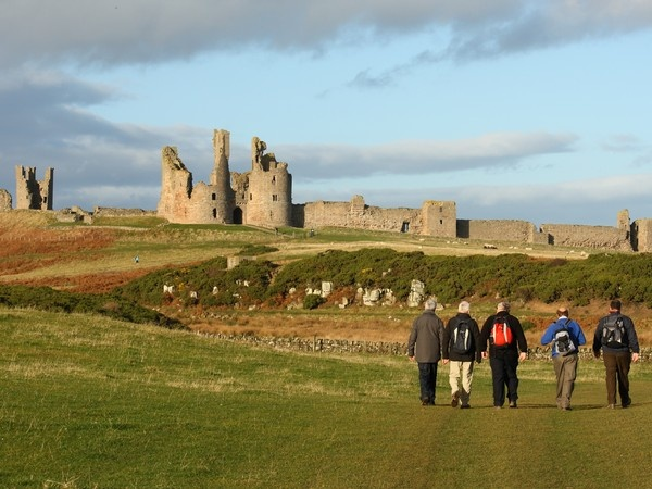 Walkers approaching Dunstanburgh Castle