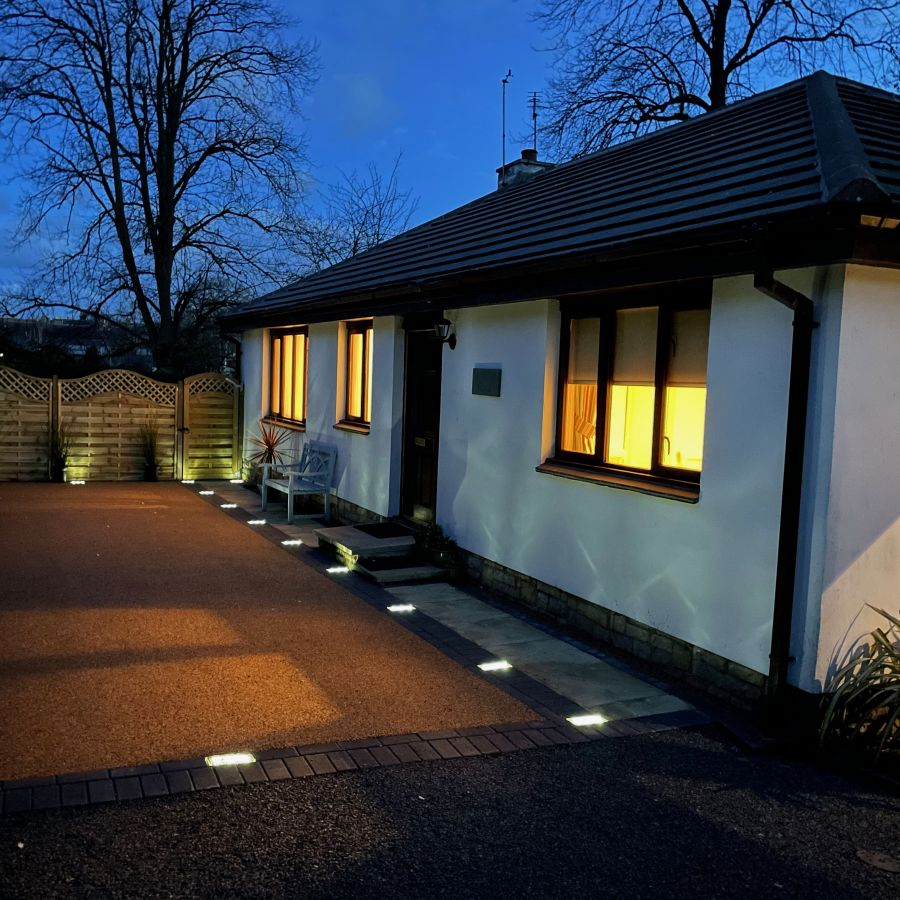 Lodge drive lit up at night.