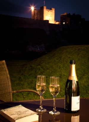 Night shot of champagne in front of Bamburgh Castle credit Coastal Retreats